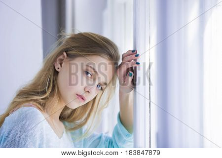 young woman with blue eyes pretty girl with cute face and blond long hair standing at window on sunny day. Future perspective and outlook
