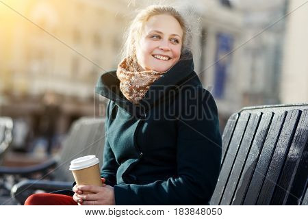 Beautiful young girl with coffee sitting on bench