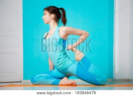 Photo of girl practicing yoga on blue background