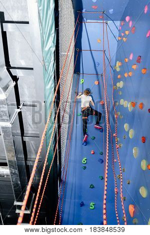 Little girl climbing a rock climbing wall indoor. Back view of girl practicing climbing skills