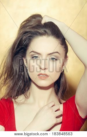 Pretty girl or beautiful woman with grey eyes and natural makeup on young face doing long blond hair behind ear on yellow wall