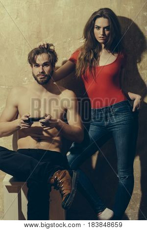 Pretty girl or beautiful blond woman in red tshirt and blue jeans touching hair of bearded man or sexy hipster with beard muscular torso chest playing with smartphone phone on beige wall