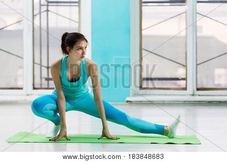 Young girl doing stretching exercise on rug