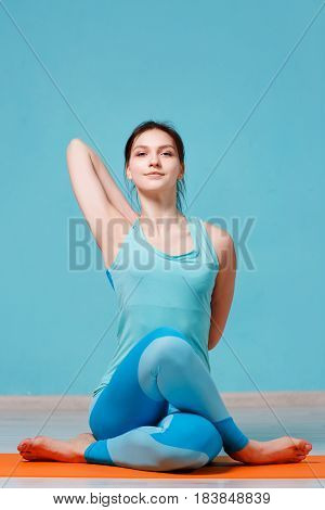 Photo of brunette practicing yoga in hall
