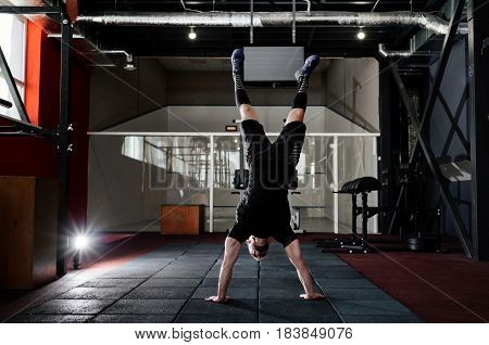 Athlete walking on his hands standing upside down in gym. Man doing push ups on his hands. Workout lifestyle concept. Full body length portrait