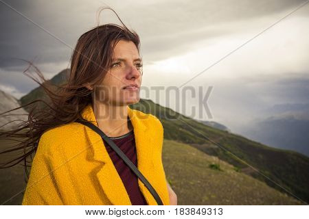 Young beautiful woman in yellow jacket at windy day on mountains background