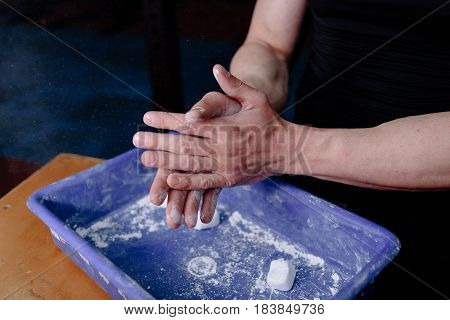 Man athlete coating his hands in powder chalk magnesium. Ready for workout training. Magnesium of gymnastic
