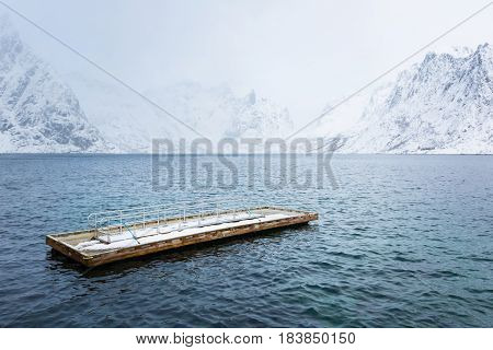Wooden floating pier in the sea against the background of snow Lofoten mountains