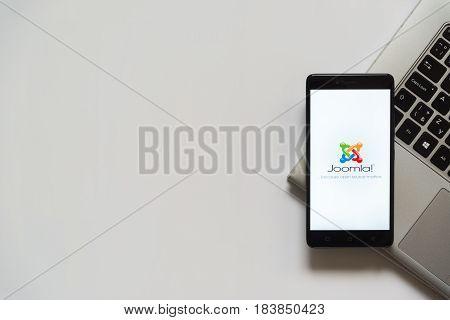Bratislava, Slovakia, April 28, 2017: Joomla logo on smartphone screen placed on laptop keyboard. Empty place to write information.
