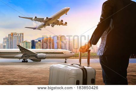 business man and traveling luggage standing in airport and passenger plane flying above