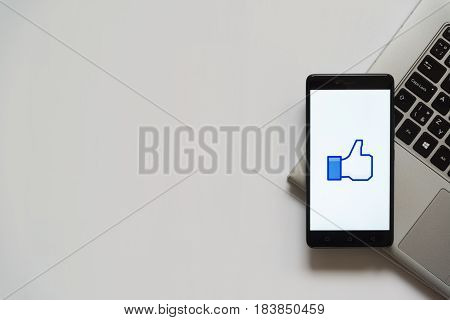 Bratislava, Slovakia, April 28, 2017: Facebook like thumb logo on smartphone screen placed on laptop keyboard. Empty place to write information.
