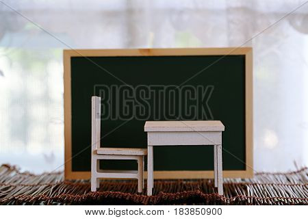 Chair table set with green board wooden decoration on blur window background