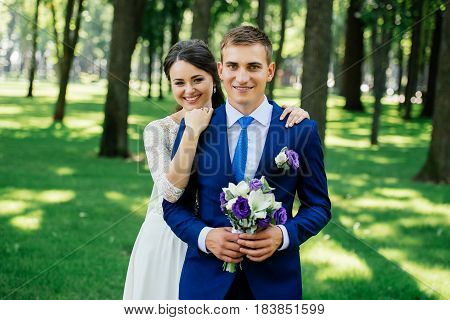 Yong beautiful smiling bride and groom hugs in the park. Bride embraces the groom. Wedding couple in love at wedding day