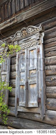 Old Dilapidated Log House With A Carved Window