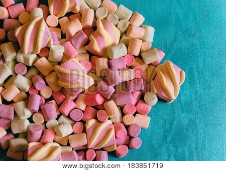 Marshmallows Background or texture of colorful mini marshmallows Handful of colorful marshmallows on a blue background