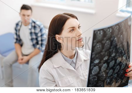 Neurological examination. Serious experienced female neurologist holding an X ray photo and examining it while standing in her office