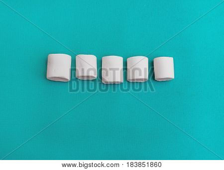 Marshmallows Background or texture of colorful mini marshmallows Five white marshmallows are lying on a blue background
