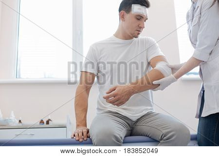Car accident. Cheerless wounded handsome man sitting on the medical bed and looking at his injury while being at the hospital