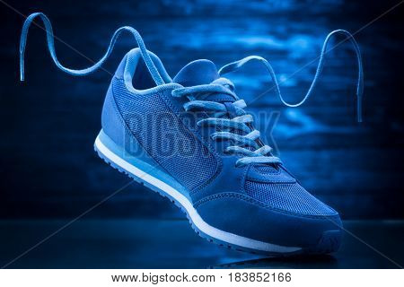 Blue sport sneakers on a wooden black background