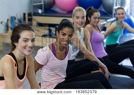 Portrait of smiling fit women relaxing in gym