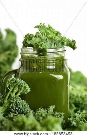 a green smoothie served in a glass mason jar surrounded by some leaves of kale and some stems of broccolini on a white background
