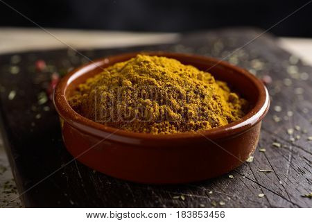 closeup of an earthenware bowl full of curry powder, on a rustic wooden chopping board, on a table