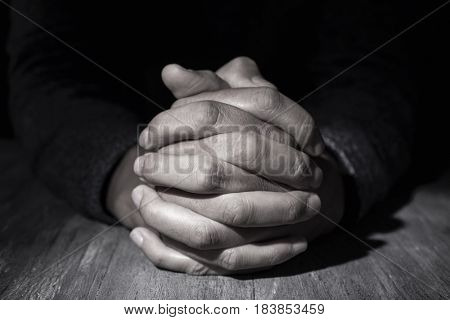 closeup of the hands of a young caucasian man with his hands clasped on a wooden table