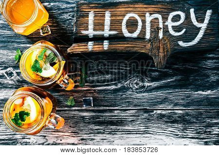 Ice tea with lemon, honey and mint in two mason jars. Black textured wood background. Wooden signboard with text 'Honey'. Top view