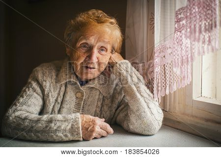 Elderly woman sitting at a loss. An old age pensioner.