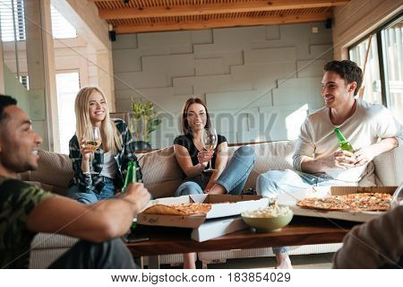 Group of happy young people with pizza, wine and beer sitting and talking at home