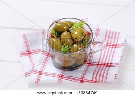 cup of marinated green olives on checkered dishtowel