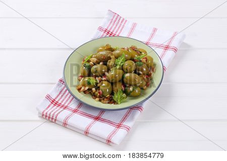 plate of marinated green olives on checkered dishtowel