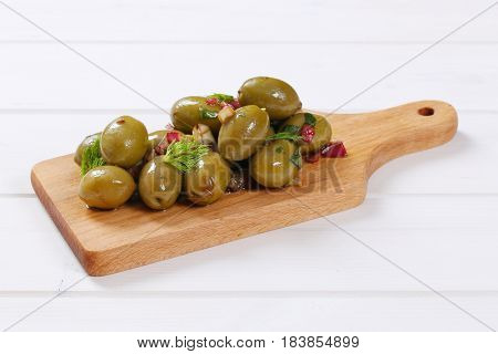 pile of marinated green olives on wooden cutting board