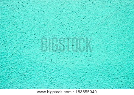 Coarse grained wall paint in cyan color.