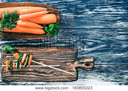 Fresh carrots and cucumber slices on black wood. Top view