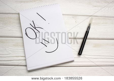 A notebook with an inscription is ok and black marker on white wooden table