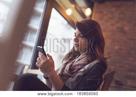 Young modern woman sitting in a cafe and typing a text message on her smart phone