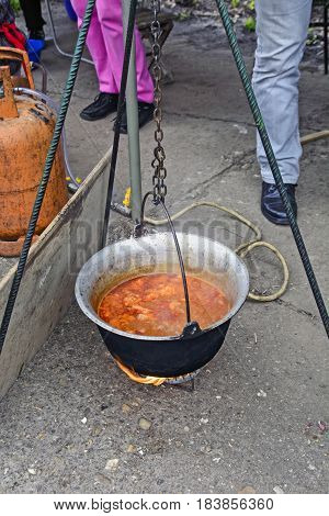 Cooking traditional stew in a kettle outdoors.