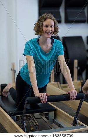 Smiling fit woman exercising on reformer in gym