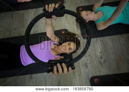 Portrait of fit woman exercising with pilates ring in gym