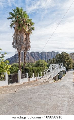 A street scene with a palm tree and pedestrian bridge in Montagu in the Western Cape Province