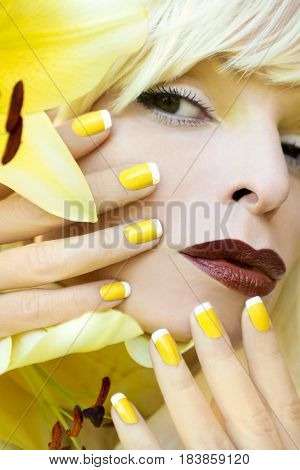Yellow French manicure for the girl with the yellow lilies in the summer closeup.