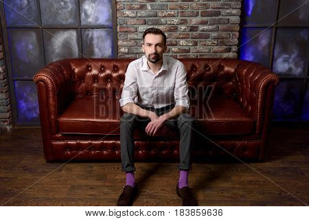 Portrait of a stylish bearded man in white shirt on leather sofa. Young confident businessman