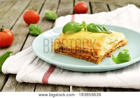 Fresh meat lasagne, lasagne bolognese, pasta dish on a wooden table with decorative basil leaf. Italian cuisine.
