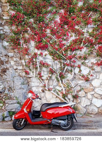Amalfi (SALERNO) Italy - June 1 2015: A red scooter parked at the edge of the road in the famous Amalfi Coast. Behind it a rock wall and rocks on which a wonderful Bouganvillea plant extends in the same red tone of the scooter.