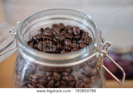 Lot of roasted coffee beans in glass jar close up
