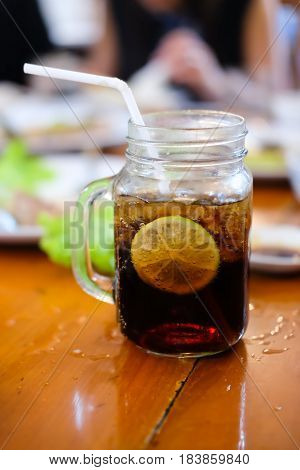Glass of soft drink with ice cubes and lemon slice
