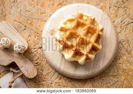 Tasty hot homemade waffles served on wooden plate