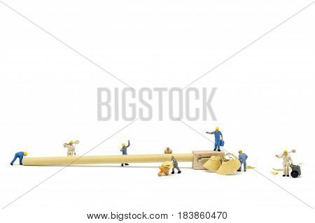 Miniature worker team sharpening a pencil on white background