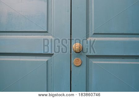 Classic wooden blue door with brass handle and lock